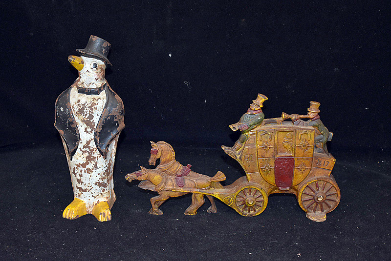 427B. Two Cast Iron Doorstops: Carriage, Penguin. | $118